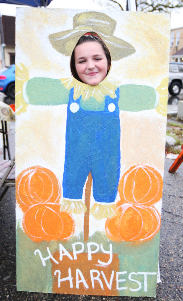 HAPPY HARVEST. Lizzie Yoder, 11 years old from Marlette, showing her smiling face through a cutout picture of a scarecrow on Main Street in Downtown Romeo during Harvest Days. (Photo by Mike Nicley)