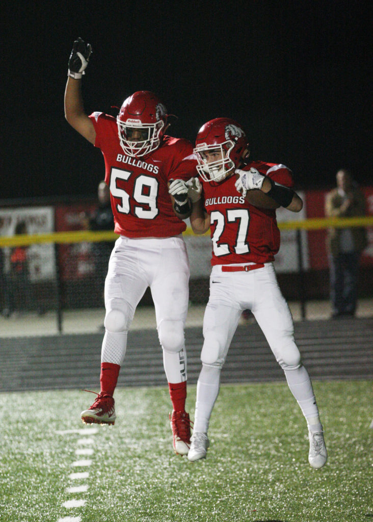 #59 Trevor Franklin and #27 John Jackman celebrating in the end zone after John Jackman scored his touchdown bringing the score Romeo 53 - Dakota 17 in the third quarter. (Photo by Mike Nicley)