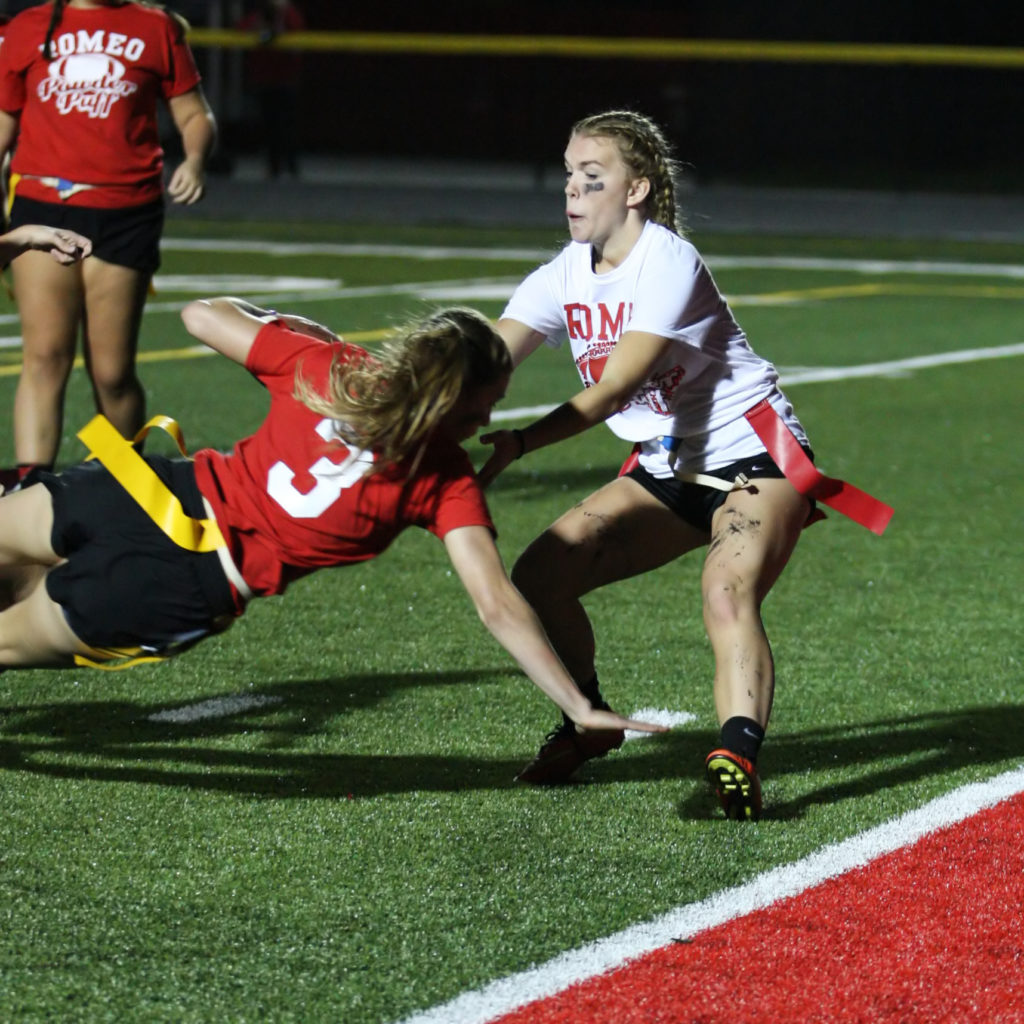 Junior Sophie Kort, #9, trying to stop senior Gabriella Purpura, #3, from scoring the extra attempt after the touchdown in the first half. (Photo by Mike Nicley)