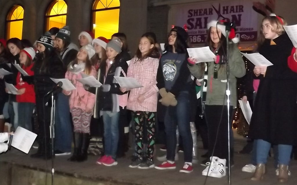 Members of the Armada Middle School and High School choirs sing Christmas carols at Armada Holly Days where Santa appeared on Saturday. (Photo by Stacy Sobotka)